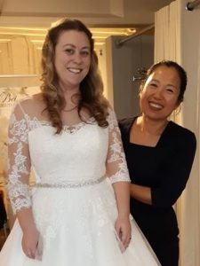 image of Bei showing a wedding dress she has made on a model