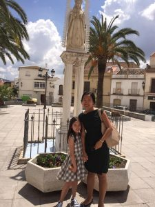 Bei standing in front of statue with her daughter on a sunny day